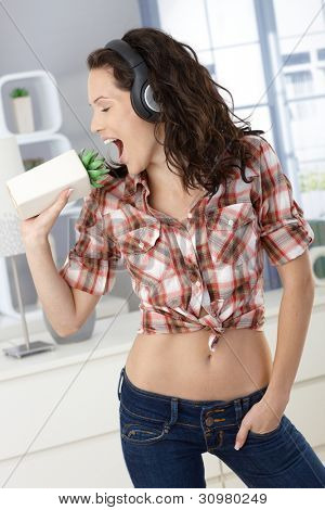 Pretty woman enjoying singing at home, as fun using plant as microphone, listening to music via headphones.