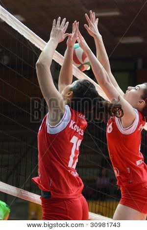 KAPOSVAR, HUNGARY - FEBRUARY 3: Kamilla Gyorbiro (R) in action at the Hungarian Championship volleyball game Kaposvar (red) vs Miskolc (green), February 3, 2012 in Kaposvar, Hungary