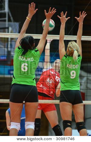 KAPOSVAR, HUNGARY - FEBRUARY 3: Karmen Kovacs (in red) in action at the Hungarian Championship volleyball game Kaposvar (red) vs Miskolc (green), February 3, 2012 in Kaposvar, Hungary