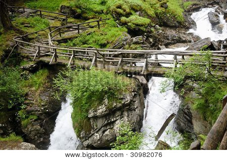 Wooden Bridge Over Saent Waterfalls In The Italian Mountains