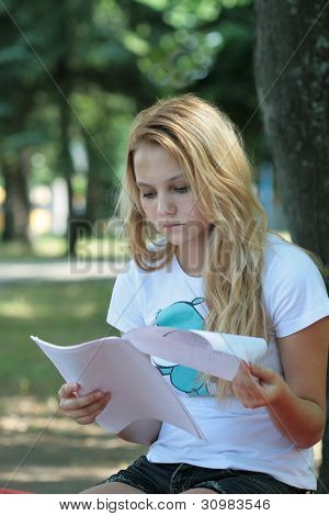 The girl reads the letter in a summer garden
