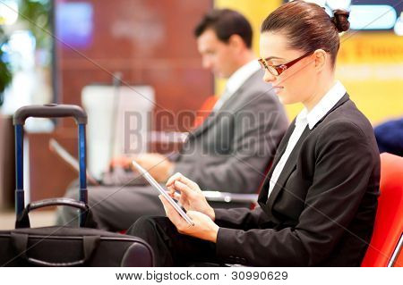 young businesswoman using tablet computer at airport while waiting for her flight