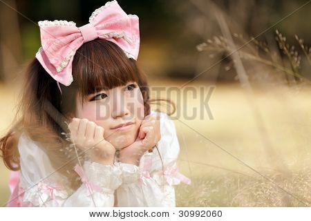 japanese woman in sweet lolita cosplay lying in meadow, tokyo