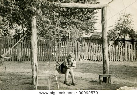 Vintage photo of child playing outdoor (fifties)
