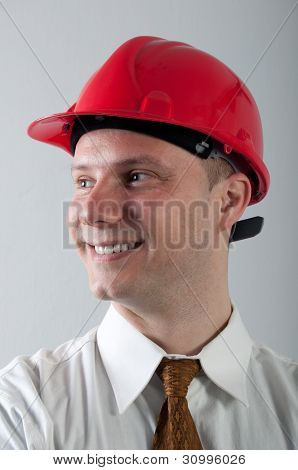 Portrait of young smiling engineer with red helmet
