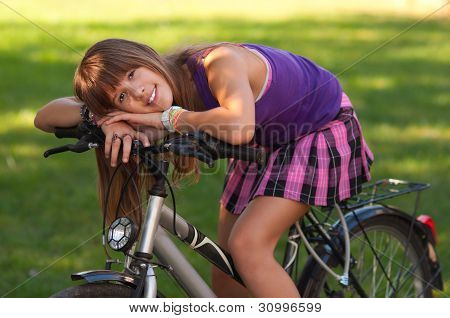 Beautiful teenage girl resting on the bicycle in the middle of the green meadow on sunny summer day