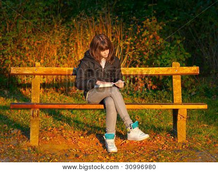 Beautiful teenage girl reads the book while sitting on the bench during autumn sunset