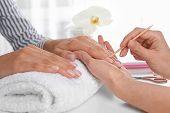 Manicurist Preparing Clients Fingernail Cuticles In Salon, Closeup poster