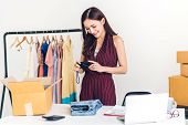 Young Woman Freelancer Working Sme Business Online Shopping And Packing Clothes With Cardboard Box A poster