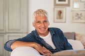 Happy senior man sitting on comfortable sofa in living room. Old man with grey hair relaxing on couc poster