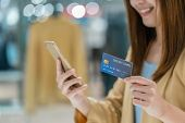 Closeup Asian Woman Using Credit Card With Mobile For Online Shopping In Department Store Over The C poster