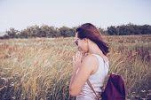 Traveler Girl Relaxing In Fields. Young Girl Traveler Relaxing In Nature. Traveler With Backpack In  poster