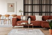 Stylish Brown Corner Sofa With Patterned Pillows In Elegant Living Room Interior With Mullions Wall poster