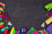 School Supplies Border Frame. Top View On A Chalkboard Background With Copy Space. Back To School Co poster