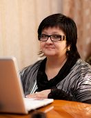 stock photo of senorita  - Office Woman indoors with a laptop - JPG