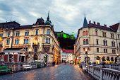 Ljubljana, Slovenia. Famous Triple Bridge In Ljubljana, Slovenia. Illuminated Castle At The Backgrou poster