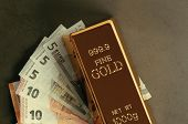 Gold Metal Ingot In Ingots On The Background Of Euro Banknotes. poster