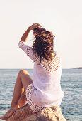 Traveler Girl Relaxing On Beach. Young Girl Traveler Relaxing In Vacation. Traveler Relaxing On Rock poster