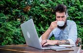 Visiting Internet Cafe. Hipster Enjoying Tea And Free Wifi In Outdoor Cafe. Bearded Man Drinking And poster