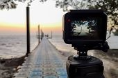 Camera Mounted On A Tripod Photograph The Pier And Sunrise, Focus On Screen. poster