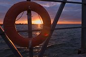 Lifebuoy On The Old Pier Against The Backdrop Of A Colorful Sunset And The Waving Sea. Life Buoy Att poster