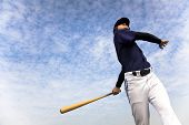 image of swings  - baseball player taking a swing with cloud background - JPG