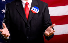 picture of politician  - A politician or business man standing in front of an American flag stumping or pleading with people to vote exercise privilege as an American citizen - JPG