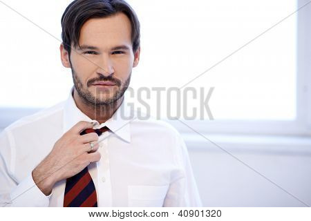 Attractive man standing adjusting the knot of his tie, head and shoulders portrait with copyspace