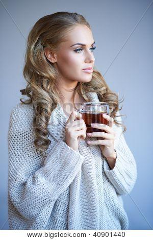 Schöne junge blonde Frau in eine stilvolle warme Winter oben stehende Tagträumen wie sie eine Becher o genießt