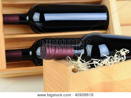 Closeup of red wine bottles in wood crates. Shallow depth of field.
