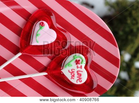 Valentine's lollipops on striped plate