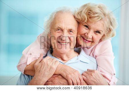 Happy elderly couple hugging in front of the camera