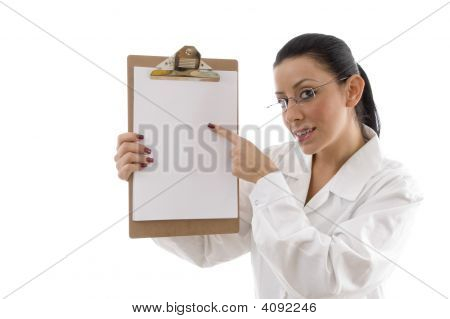 Portrait Of Female Doctor Pointing Writing Pad On White Background