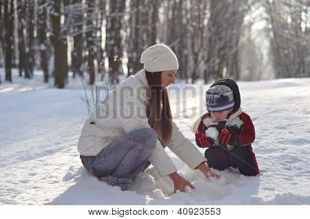 Young Mother Making Snowballs For The Baby On A Winter Walk In The Park