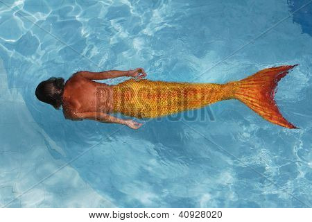 young woman mermaid swimming in water