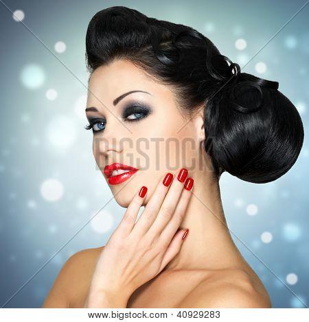 Moda mulher com lábios vermelhos, unhas e penteado criativo