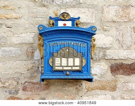 German Blue Mailbox On The Brick Wall