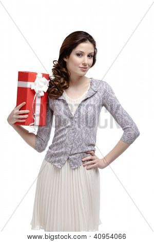 Young woman hands a holiday present wrapped in red paper, isolated on white