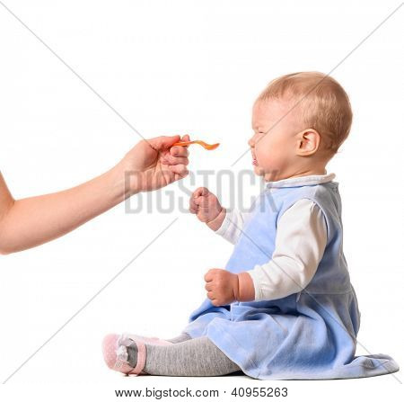 tasteless. woman is feeding her baby with a spoon
