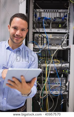 Man with tablet pc working in data centre