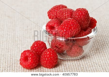 Still life with red raspberry and glass bowl on gray linen table cloth, copy space design ready
