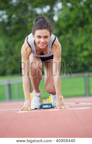 Female athlete at athletic starting blocks on track field