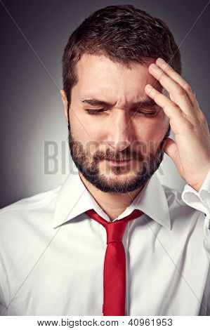 portrait of man with headache over grey background