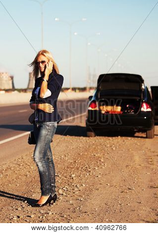 Young woman with broken car calling on the phone