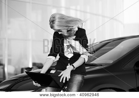 Young businesswoman using laptop against office windows