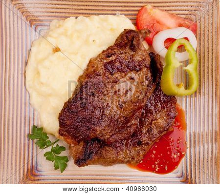Baked beef steak with mashed potato, on the decorative plate, served on the table - high angle view
