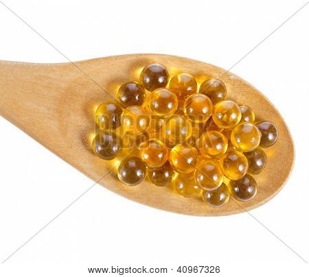 oil pills on spoon isolated on white background