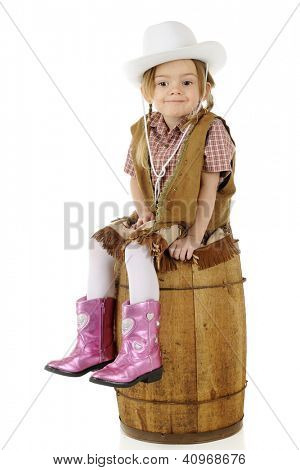 An adorable preschool cowgirl sitting on a rustic wood barrel looking smug.  On a white background.