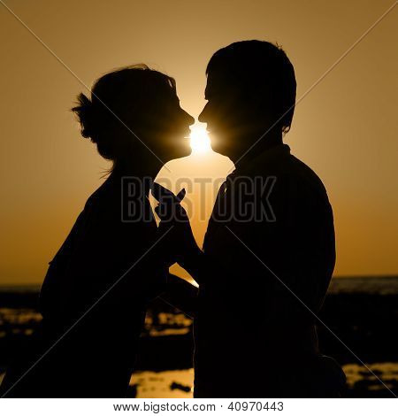 Sillhouette Of Kissing Couple At Sunset