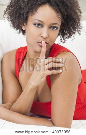 A beautiful mixed race African American girl or young woman wearing a red dress with her finger on her lips asking for silence or keeping a secret